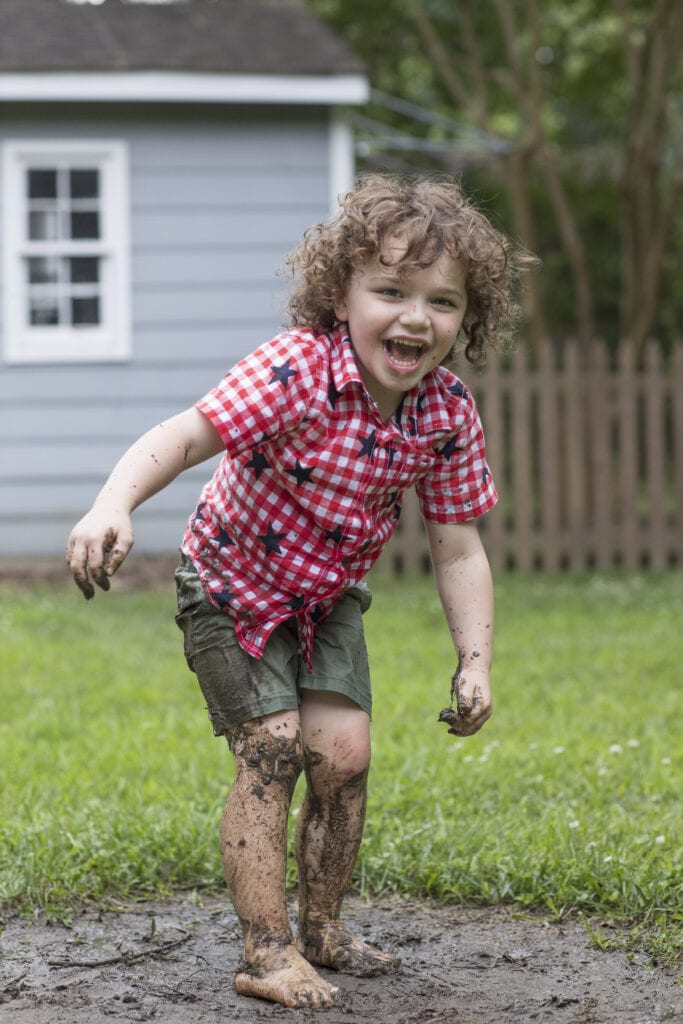 Little boy playing in a mud puddle after the rain