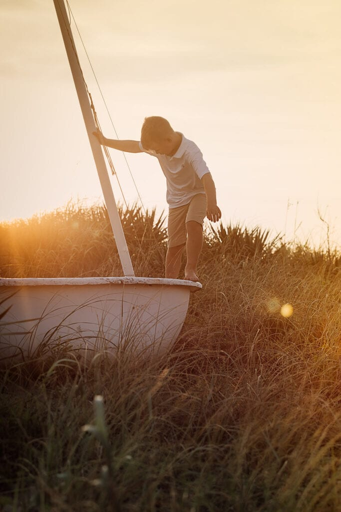 Boy on sailboat at sunset