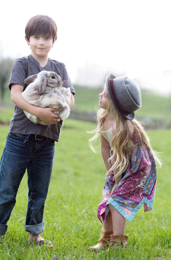 Boy and girl on the farm with animals