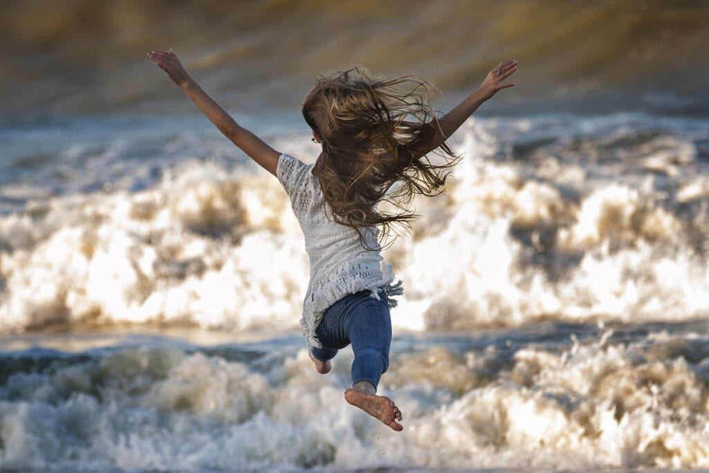 Girl dancing in Ocean waves corolla NC