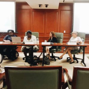 Panelists of the Olmstead at 20 event sit at a table in the front of the conference room