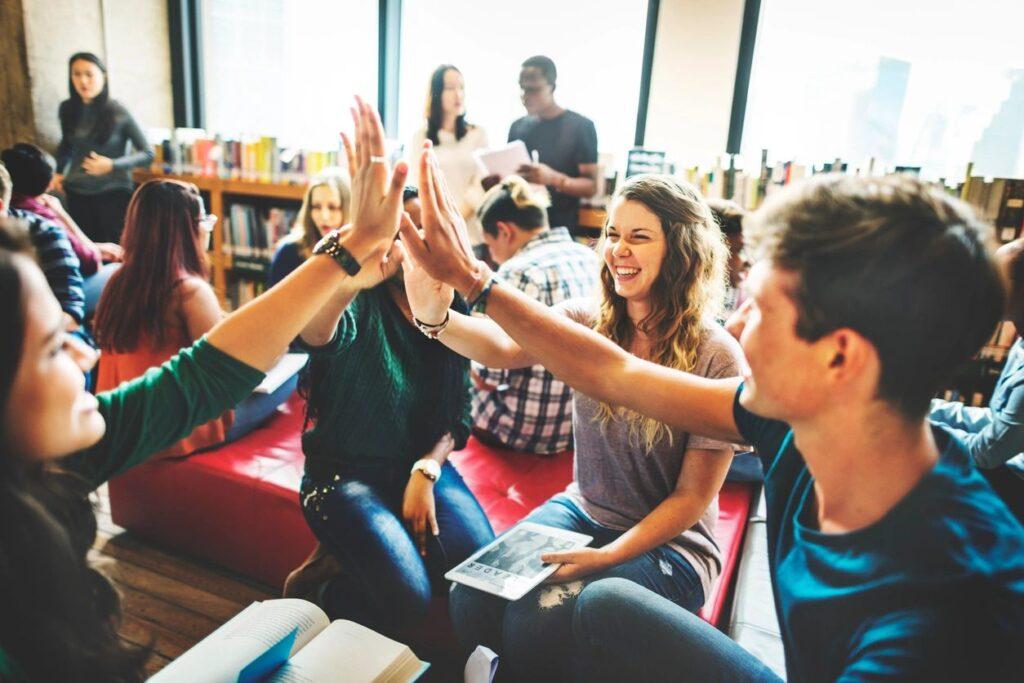 Photographie de quatre adolescents souriants assis en rond dans une bibliothèque, se tapant dans les mains au centre du cercle.