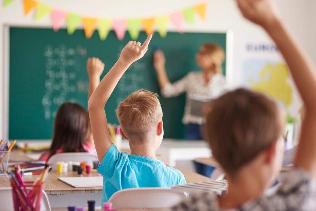 Photographie de trois enfants, de dos et un en arrière de l'autre, levant la main dans leur classe lors d'une leçon de mathématique.