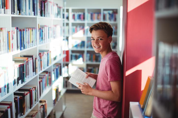 Photographie d'un adolescent souriant tenant un livre dans une bibliothèque.