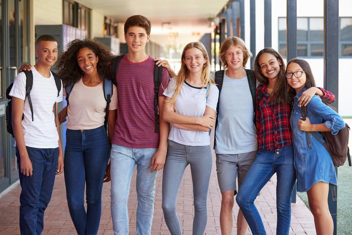 Photographie d'un groupe d'adolescents réuni dans le corridor de leur école.