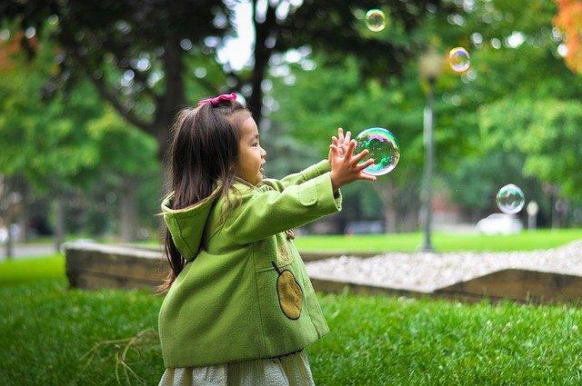 Photographie d'une jeune enfant dans un parc essayant de prendre dans ses mains une grosse bulle en l'air.