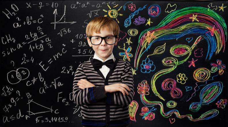 Photographie d'un enfant devant un tableau noir. Le tableau à sa droite est rempli de formules mathématiques et à sa gauche, d'illustrations colorées artistiques.