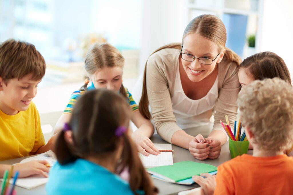 Photographie d'une jeune enseignante souriante entourée d'élèves attentifs.