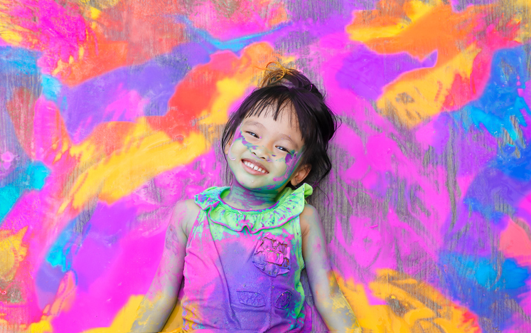 Photographie d'une jeune enfant couchée dans de la peinture colorée.