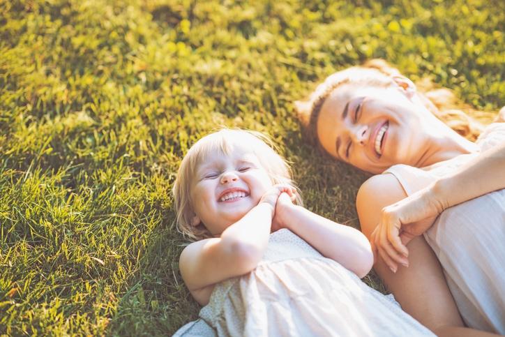 Photographie d'une jeune mère et de sa fille riant aux éclats, couchées sur le gazon.