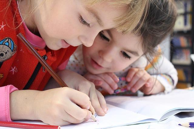 Photographie de deux enfants d'âge préscolaire qui écrivent dans un cahier d'activité.