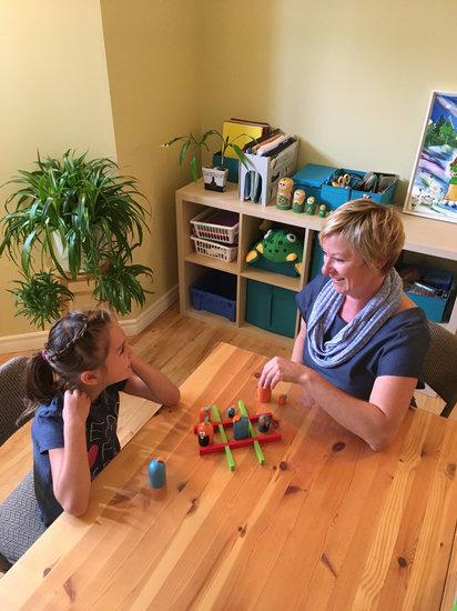 Photographie de Josée Bellehumeur, enseignante consultante en focusing, enseignant à une jeune fille une stratégie à l'aide d'une activité ludique.
