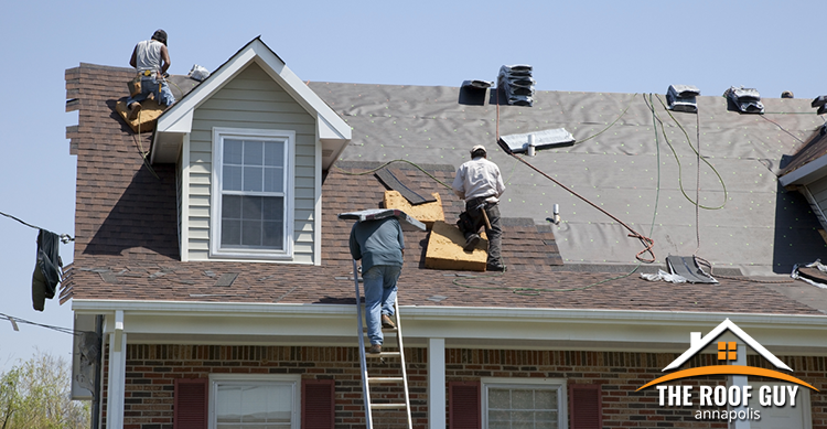 Crew of roofers completing a roof replacement.