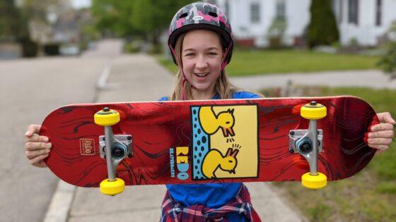 Eva holding the Eye Candy Pop Barking Ducks skateboard