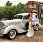 Wedding couple in front of a vintage wedding limo