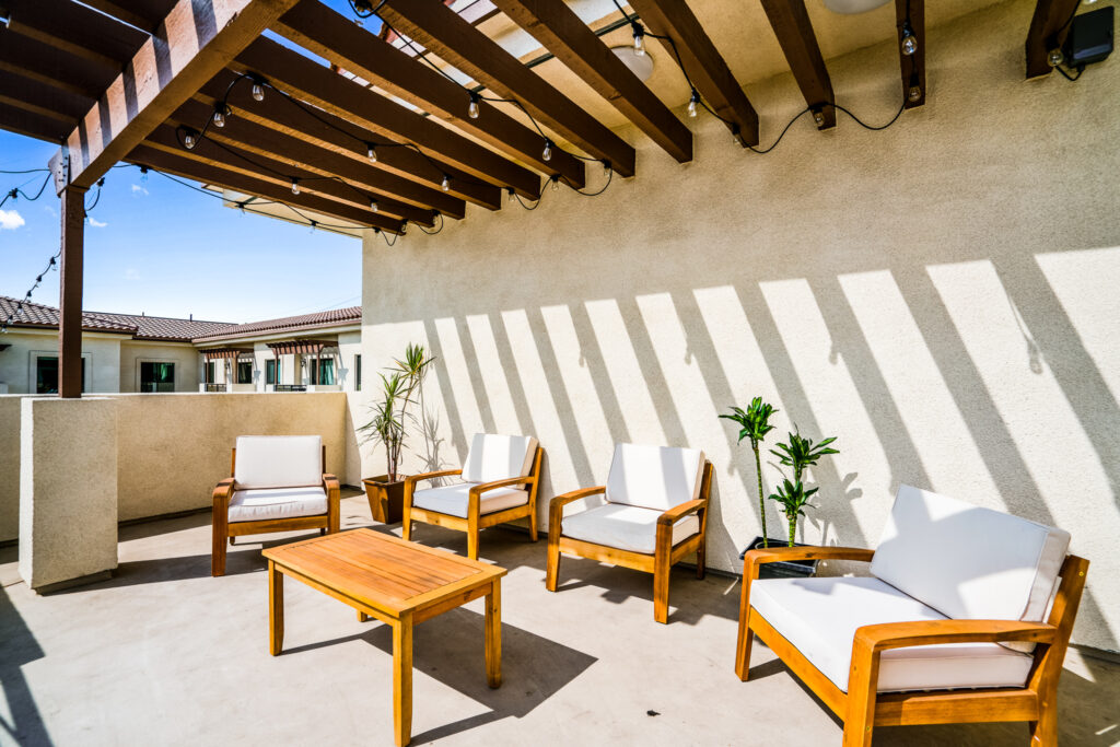 Cushion-covered wood furniture with plants on the elevated community patio at Gladstone Senior Villas.