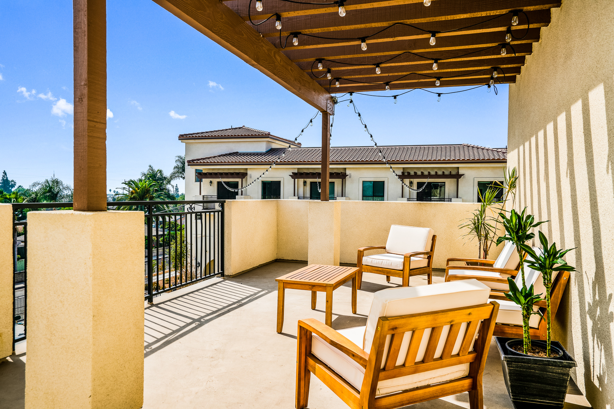 Communal outdoor balcony area featuring cushioned wood furniture at Gladstone Senior Villas.