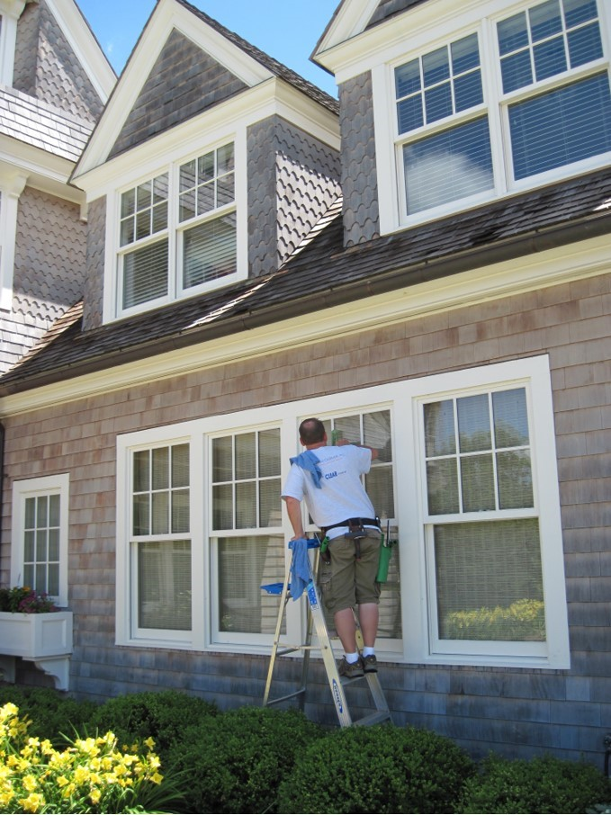 Man cleaning windows outside a home