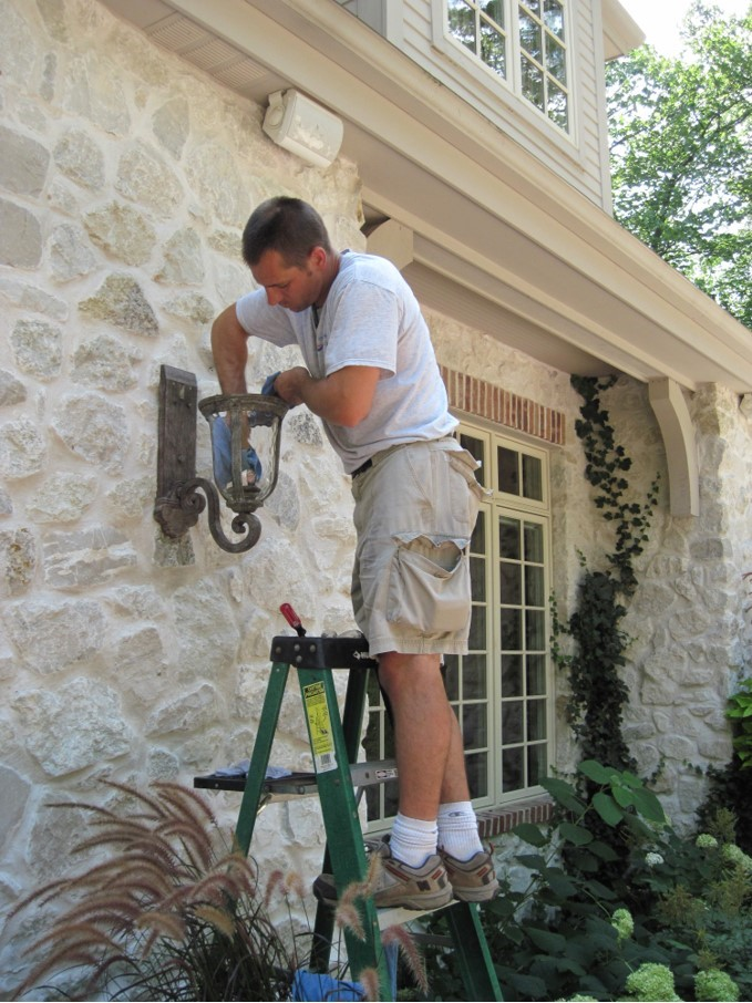 Man cleaning lights on outside of house