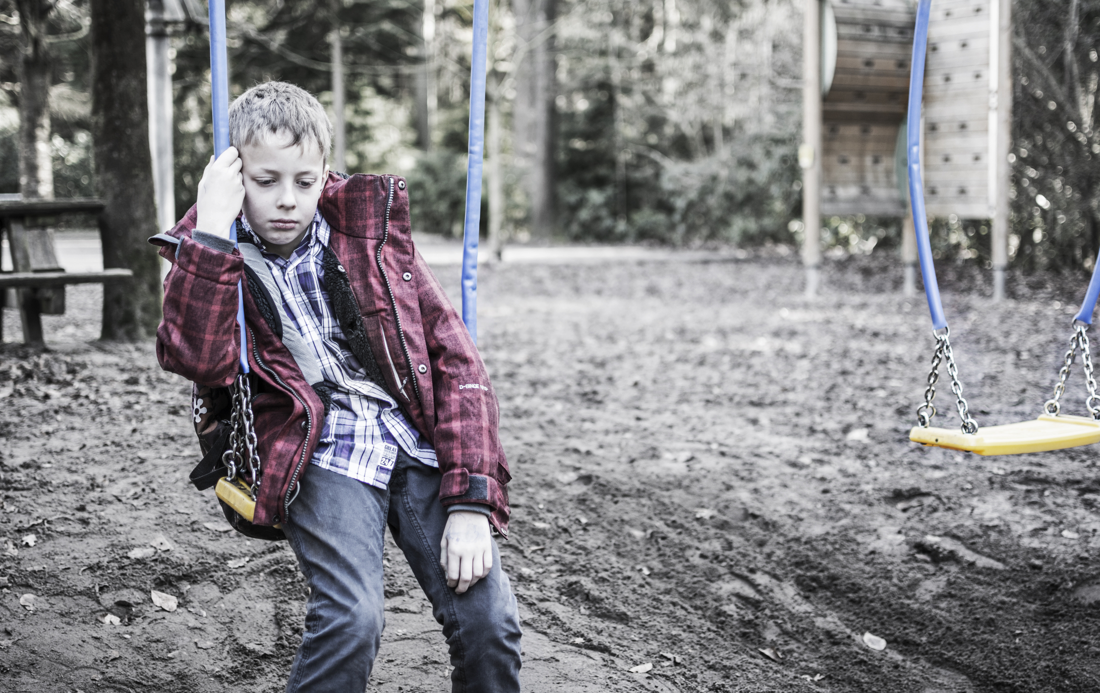 neglected young boy on a swing