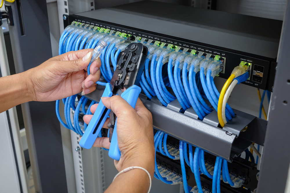 Two hands installing network cabling by CKC Data Solutions