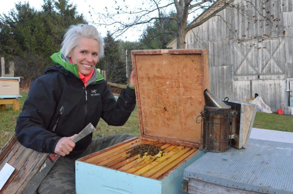 Sophie sur son terrain avec une ruche ouverte