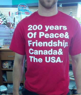 "An image of store staff wearing a t-shirt saying ""200 years of Peace & Friendship, Canada & the USA"""