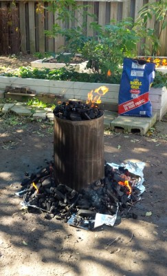 The trash can has been placed over the turkey, charcoal is surround the can, and on top of the can.
