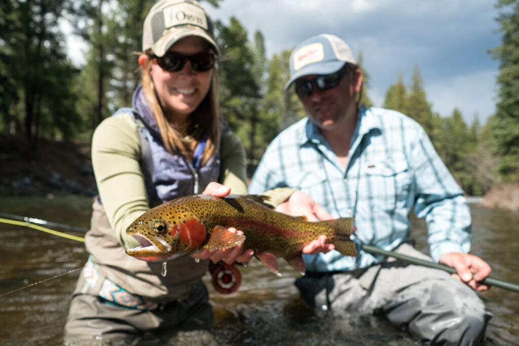 People holding a brown trout in San Juan River, CO