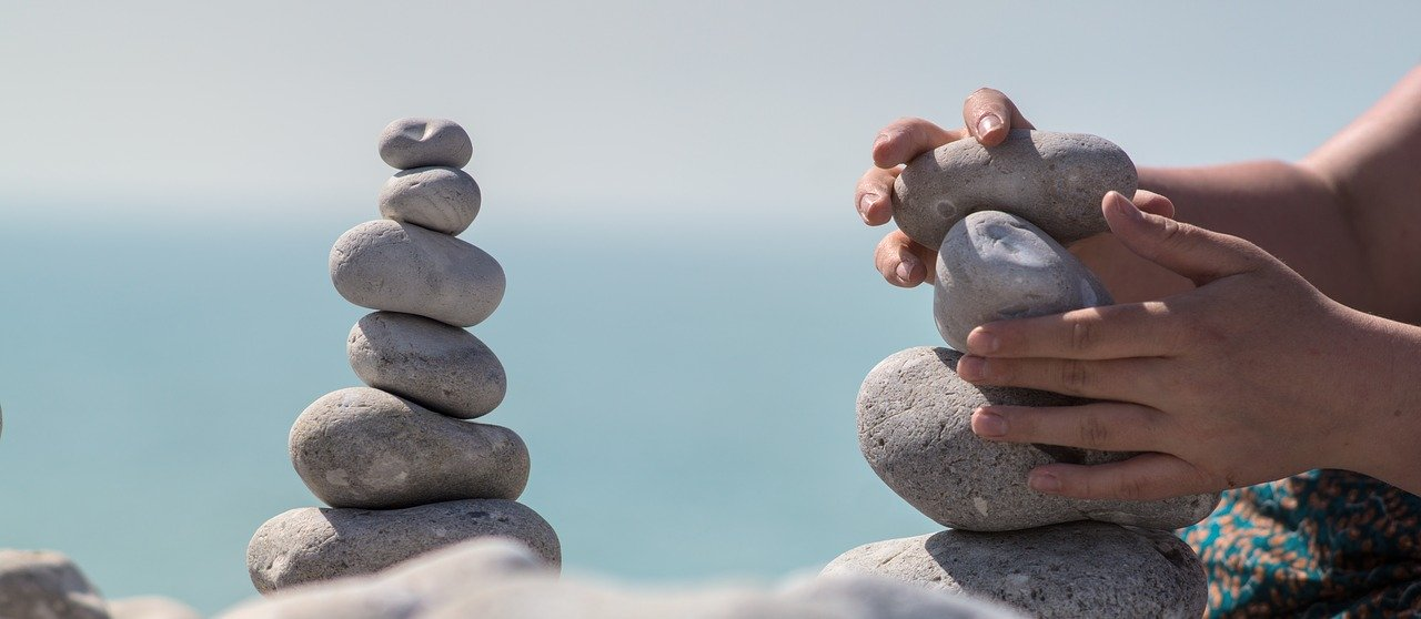 A Patience person stacking rocks by the sea