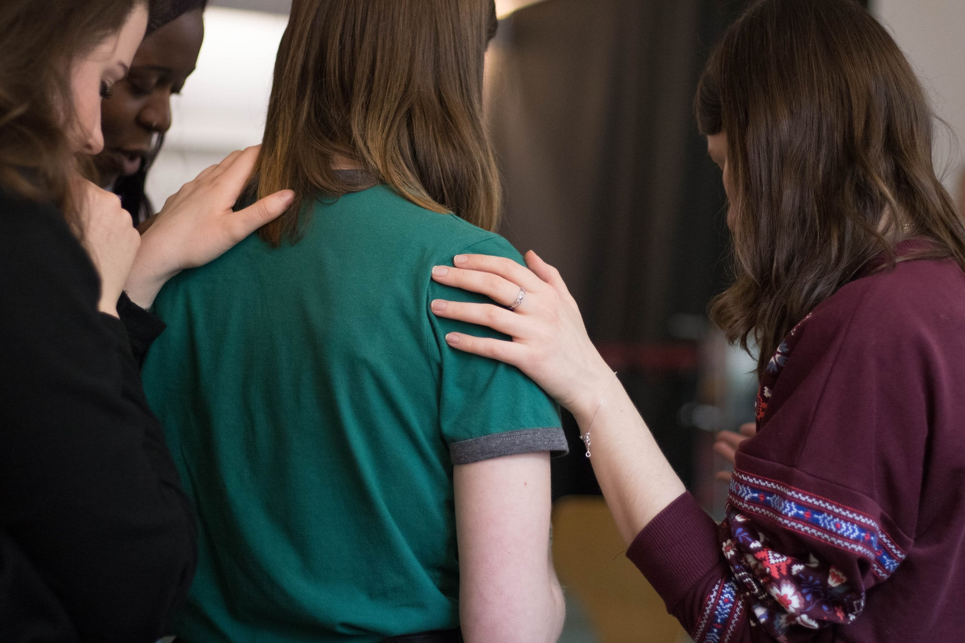 Both Judgement and Compassion shown to a Women being comforted by her friends.