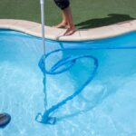 person cleaning pool with vacuum