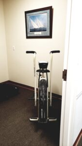 Unlike other types of exercise bikes with fixed handles, an air bike has handles that move with your peddaling action, so you get a full upper body workout as you work your legs. ... An air bike uses wind resistance via a large fan – so the harder you work, the more resistance you feel.