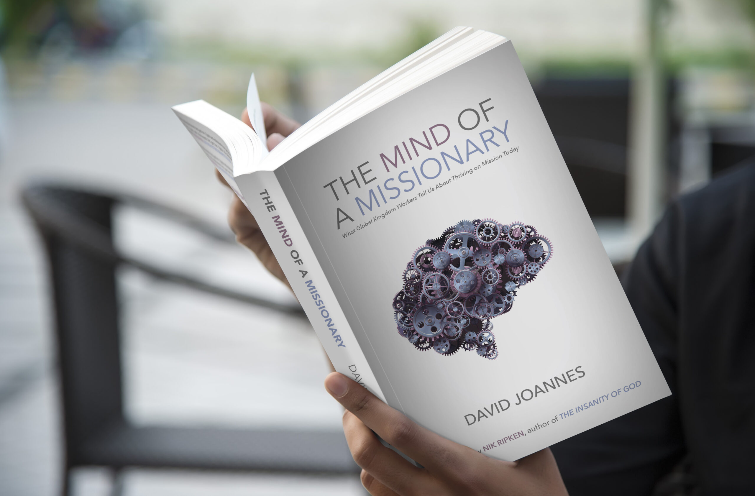 man holding the book The Mind of a Missionary