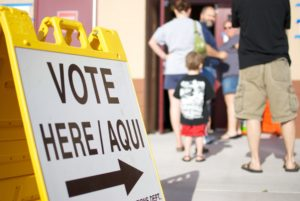 Yellow sign with VOTE HERE is standing by a line of people wating to get to the polls in Arizona