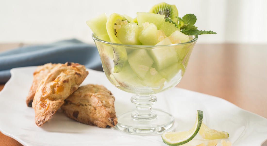 Scones and a bowl of fruit on a white plate