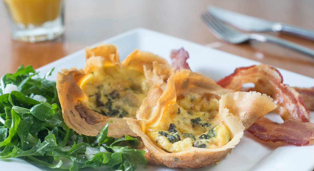 Quiche cups on a white plate with arugula and bacon and a cup of orange juice and silverware