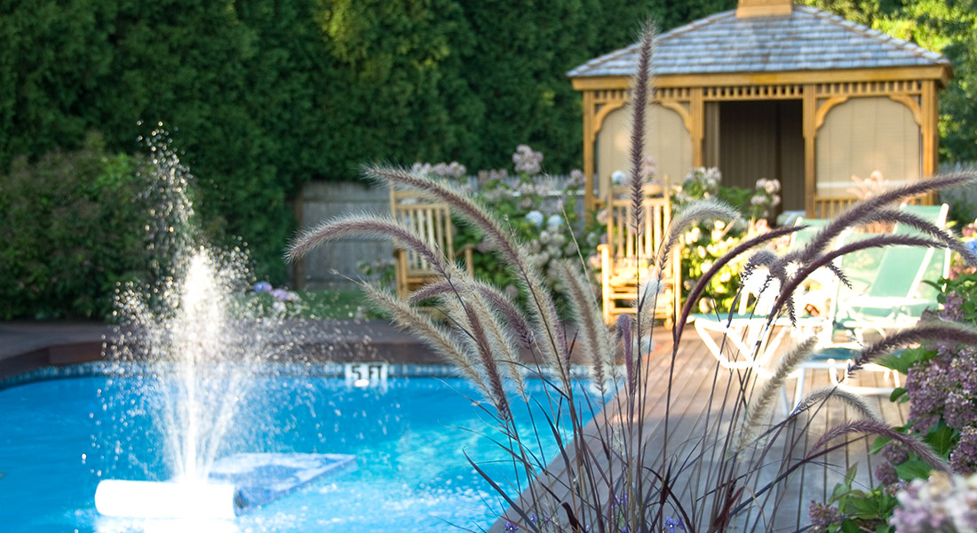 Pool with a fountain and gazebo in the background surrounded by plants all around