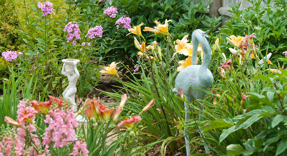 Beautiful gardens with blooming yellow and orange lilies and statues