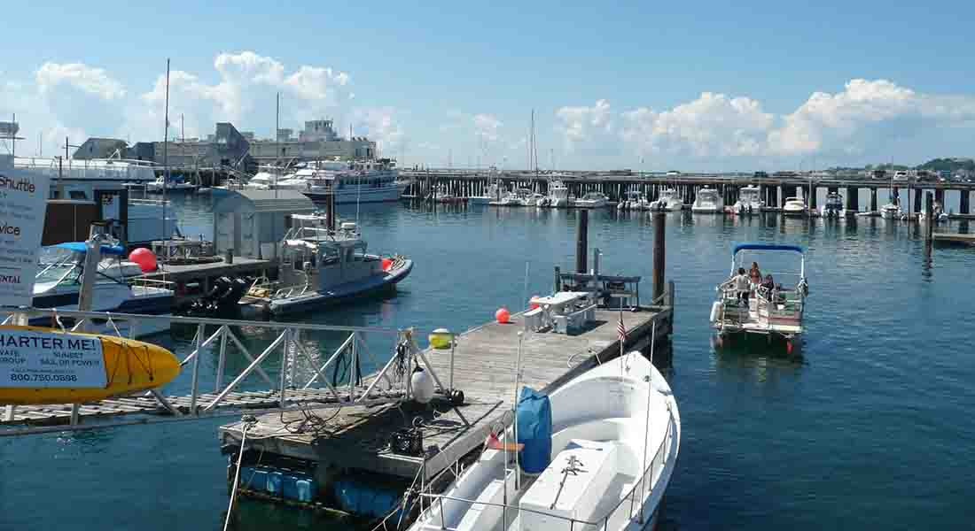 Cape Cod harbor with blue sky and water colors and small and large vessels.