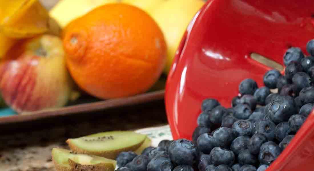 Orange, apple, kiwi, and blueberries on a granite counter