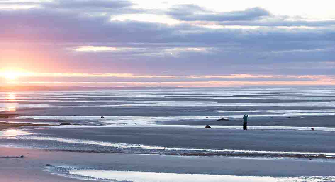 The sun setting at low tide on the tidal flats with people walking on the sandbar
