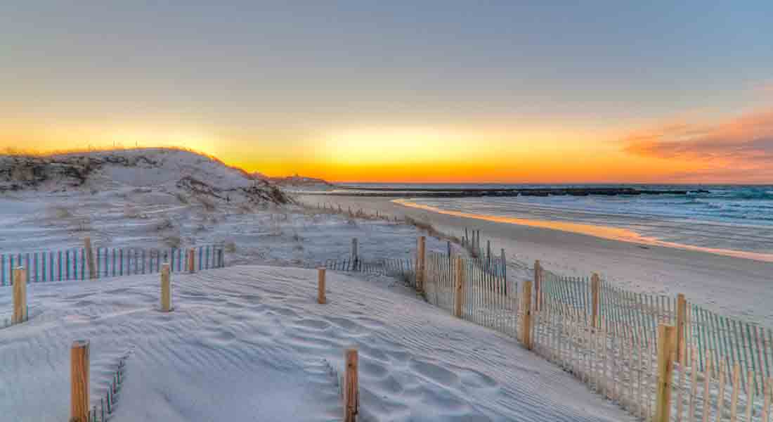 A beautiful winter sunset scene with yellow colors. The blowing sand made the beach look very white.