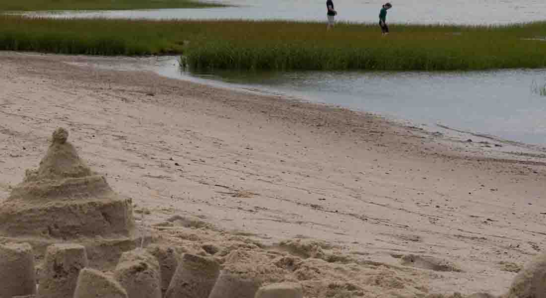 A sand castle on Cape Cod bay is left behind as a couple explores the green sea grass at low tide.