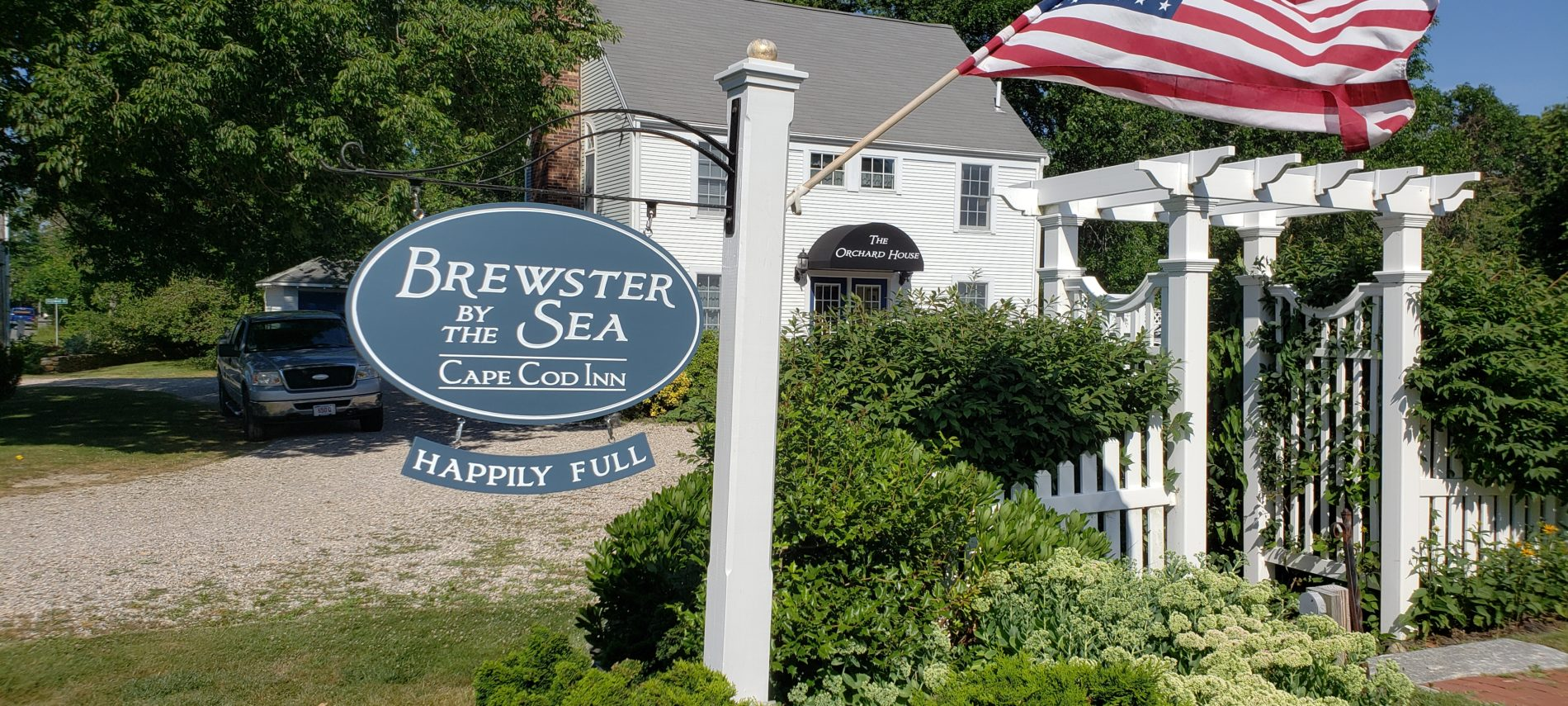 Outdoor sign at Brewster By The Sea Inn next to bushes with an American flag flapping in the wind