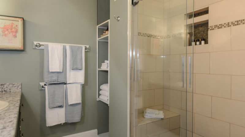 Acorn Bathroom showing a glass shower with seat, two racks with towels, and a granite countertop.