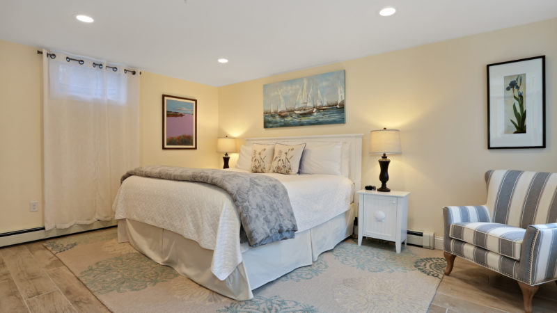 The spacious Patio Suite bedroom with the bed, two nightstands with lamps, and a lounge chair.
