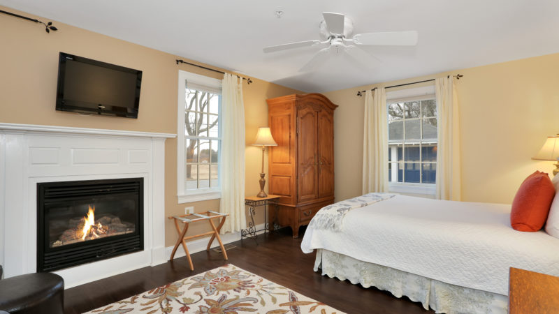Beach Blossom room showing a lit fireplace with TV above it, ceiling fan, wooden amoire, and a window with white curtains.