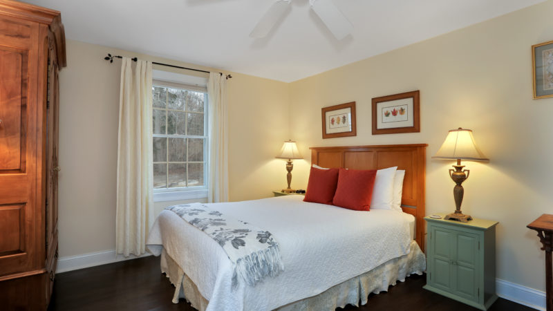 Beach Blossom room showing a bed with a wooden headboard, two end tables with lamps, ceiling fan, wooden amoire, and a window with white curtains.