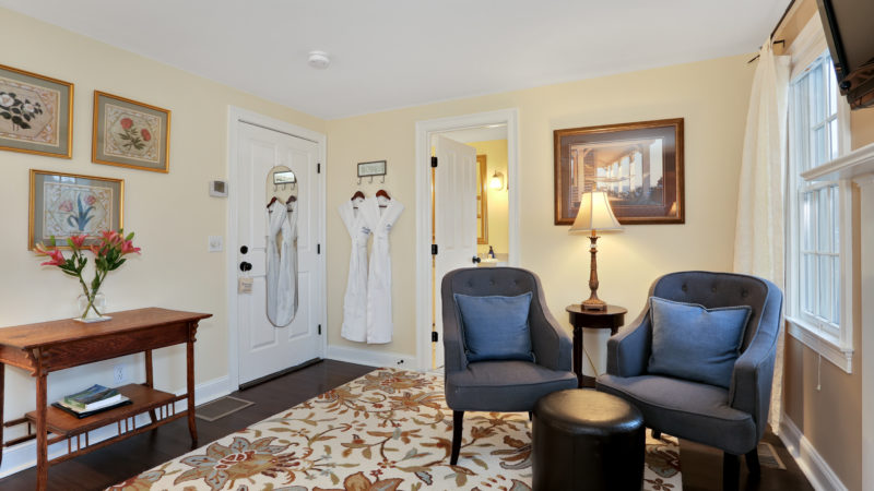 The living area in Beach Blossom room showing two gray lounge chairs with black ottoman, entry table, and door ajar to the bathroom.
